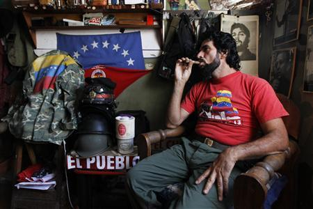 "Lopez, known as ""El Che"", smokes a cigar at his house in Caracas"